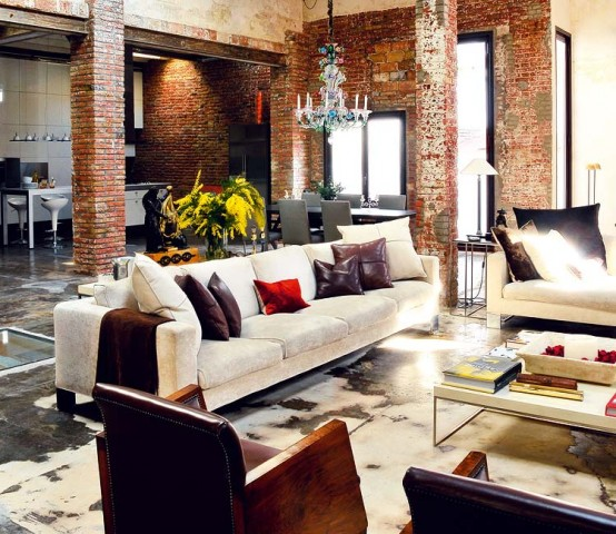I love this room.  It is a repurposed warehouse apartment with exposed brick walls and columns, concrete acid stained floors, huge windows, a very grand scale space but it is warm and friendly.  The clean lined furniture with complimenting yet simple furnishings of leather and fabric cushions and the quirky chandelier gives the space true individuality.  Industrial styling success!  Image from faisalcarper.net